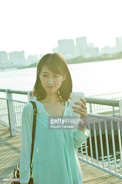 young woman drinking coffee at riverside - ショルダーバッグ ストックフォトと画像