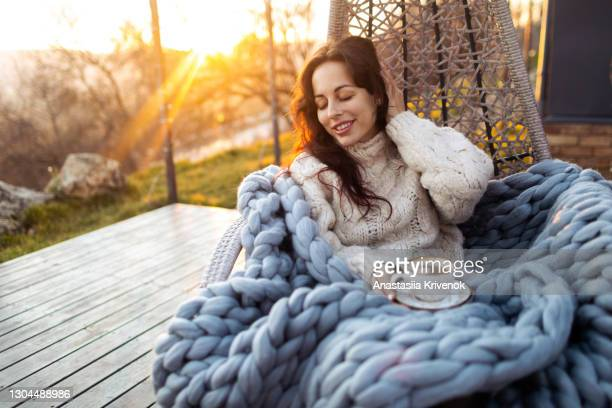 young woman drinking coffee at the beautiful terrace in the swing chair. - balcony stock pictures, royalty-free photos & images