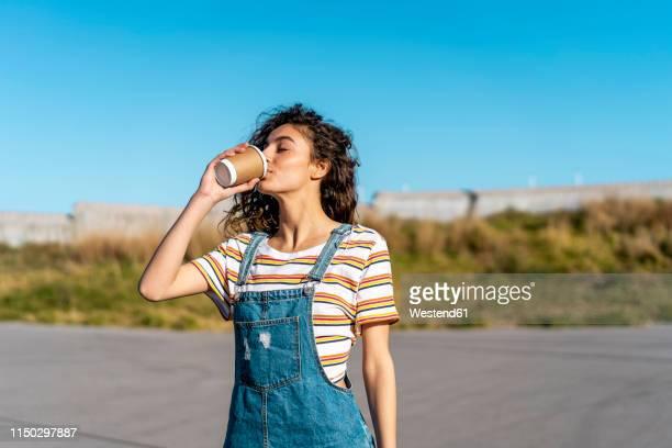 young woman drinking coffee from a disposable cup - café bebida imagens e fotografias de stock