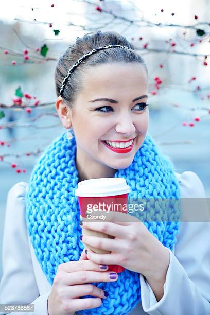 Young woman drinking coffee from paper cup