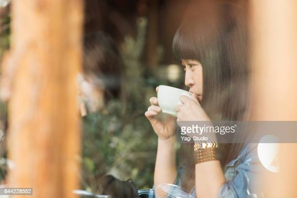 Young woman drinking coffee in a coffee shop.