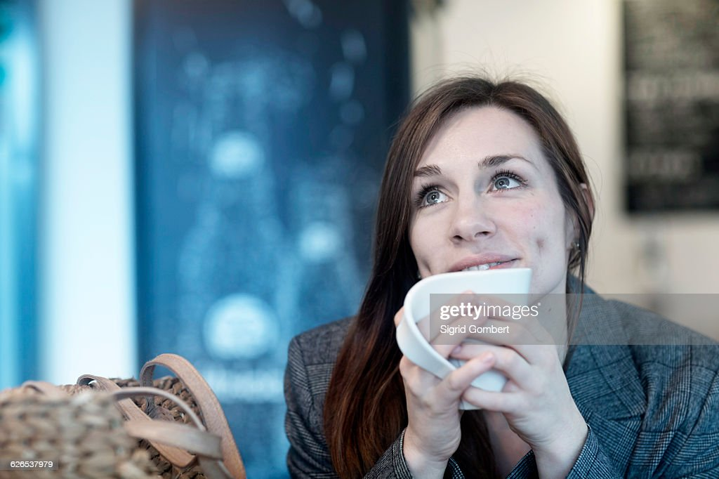 Young woman drinking coffee in cafe looking up : ストックフォト