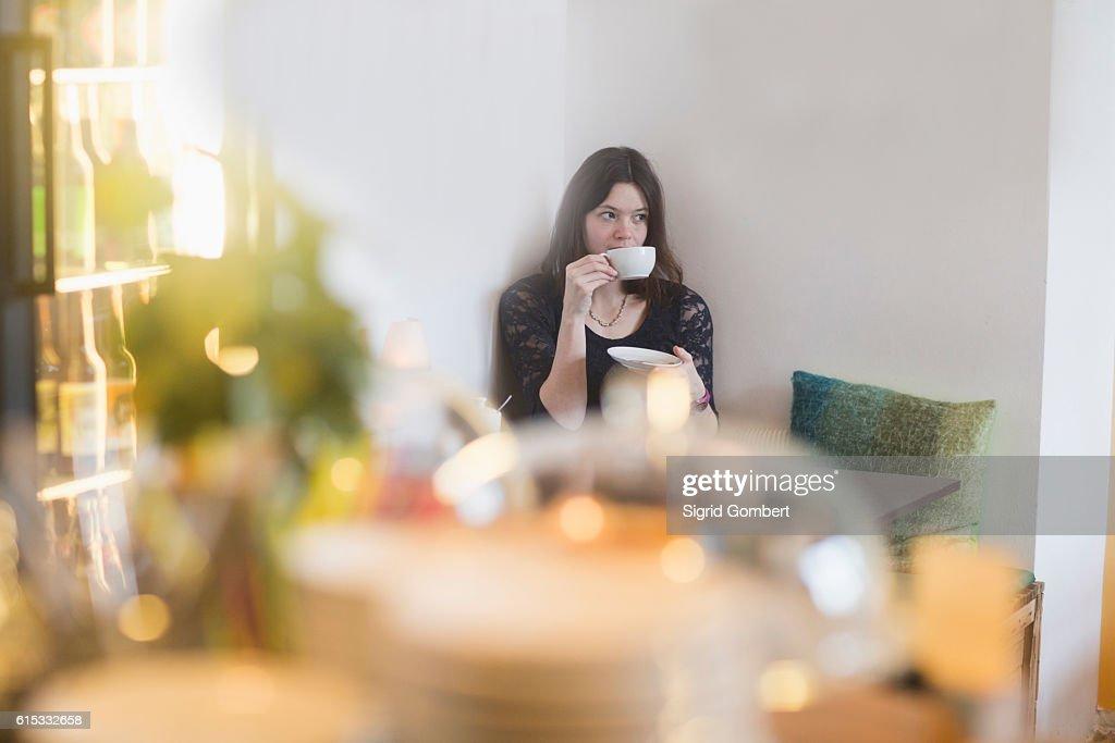 Young woman drinking coffee in coffee shop, Freiburg Im Breisgau, Baden-Württemberg, Germany : Stock Photo