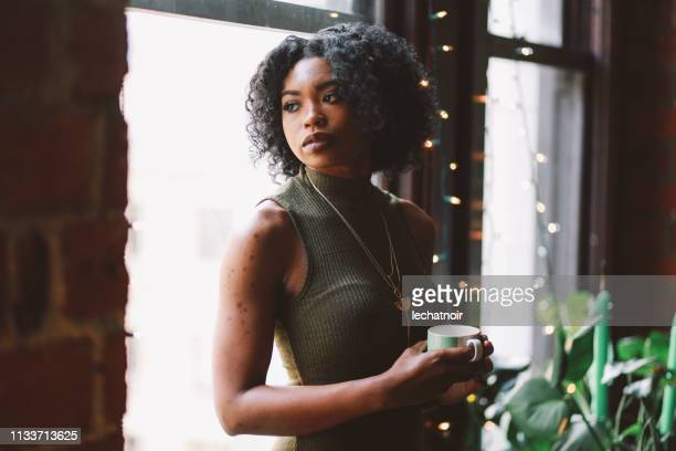 Young woman drinking coffee in her Downtown Los Angeles apartment