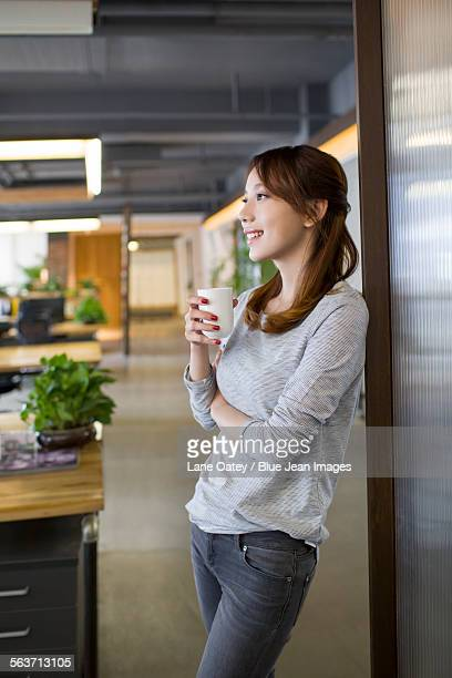 Young woman drinking coffee in office