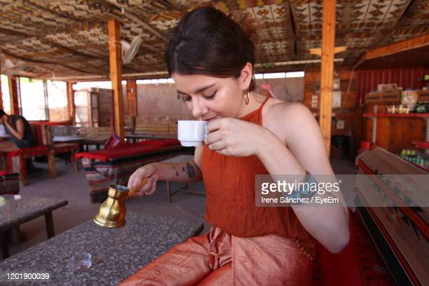 young woman drinking coffee in tent - bedouin stock pictures, royalty-free photos & images