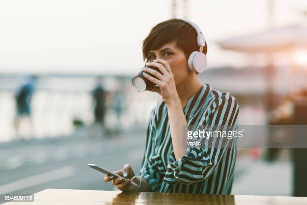 young woman drinking coffee in the city - waterfront stock pictures, royalty-free photos & images