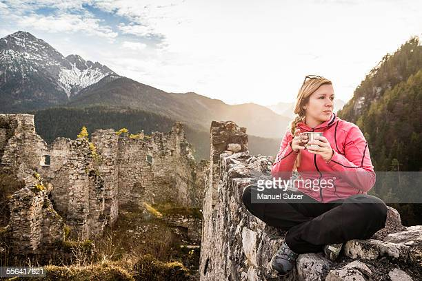Young woman drinking coffee on top of Ehrenberg castle ruins, Reutte, Tyrol, Austria