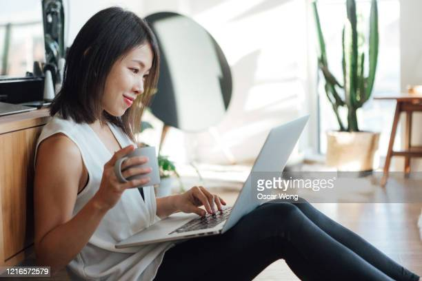 young woman drinking coffee while having a video conference at home - cheerful stock pictures, royalty-free photos & images