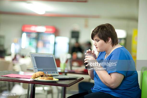 young woman drinking coke in cafe - eating disorder stock pictures, royalty-free photos & images