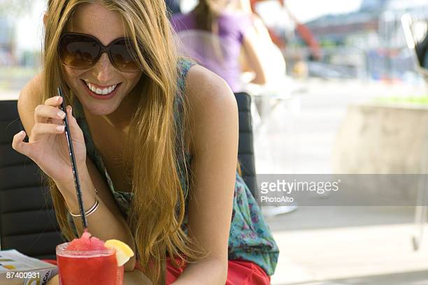Young woman drinking cool beverage outdoors