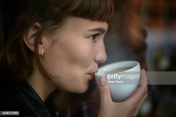 young woman drinking cup of coffee - vergnügen stock-fotos und bilder