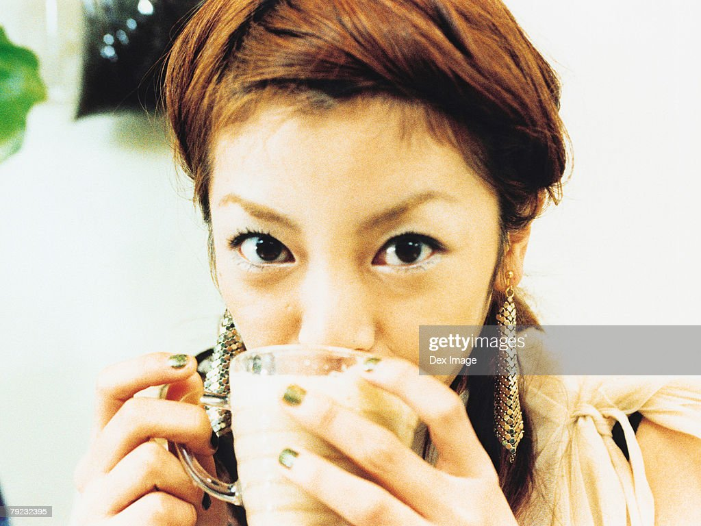 Young woman drinking cup of coffee, portrait, close-up : Stock Photo