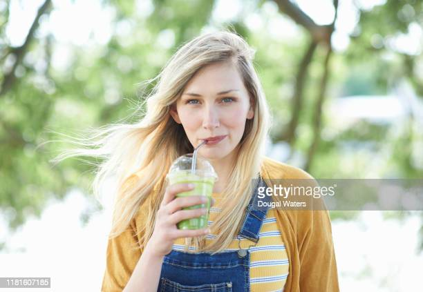 young woman drinking fresh smoothie from plastic free compostable cup. - juice drink stock pictures, royalty-free photos & images