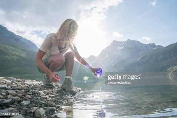 young woman drinking fresh water from mountain lake - eco tourism stock pictures, royalty-free photos & images