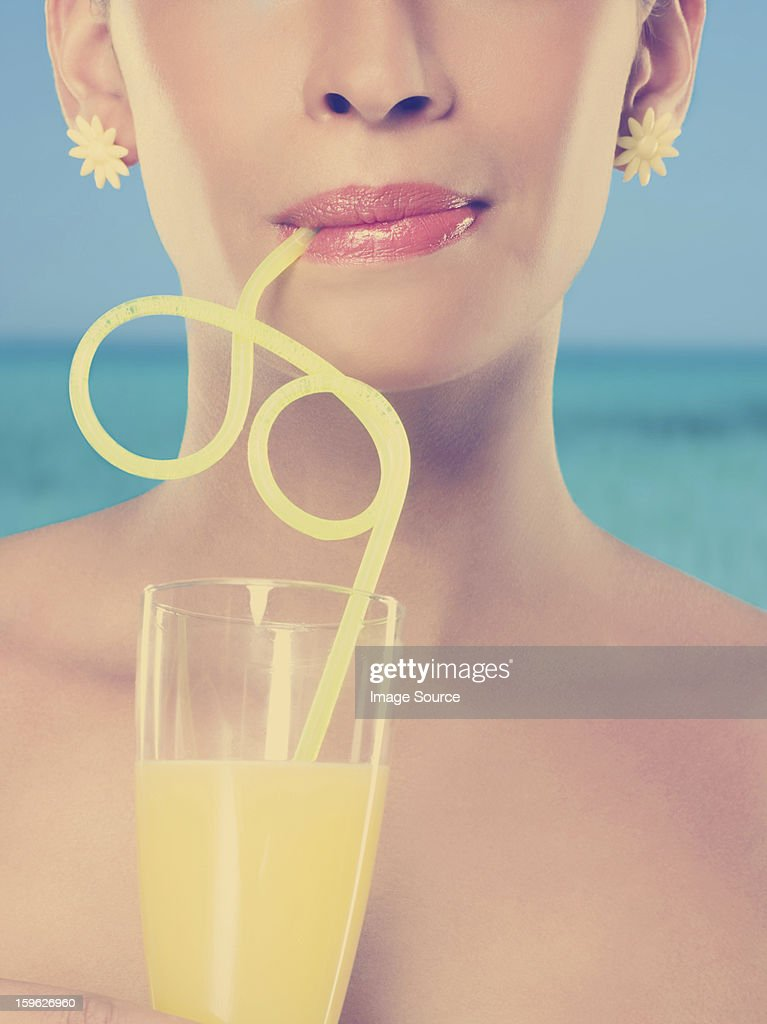Young woman drinking glass of juice with curly straw : Stock Photo
