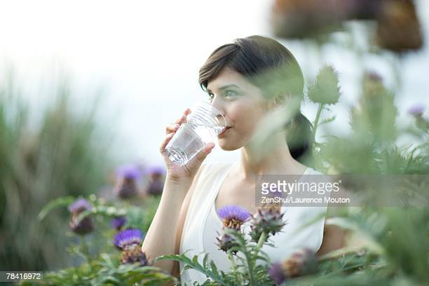young woman drinking glass of water outdoors, surrounded by thistle flowers - trinkwasser stock-fotos und bilder