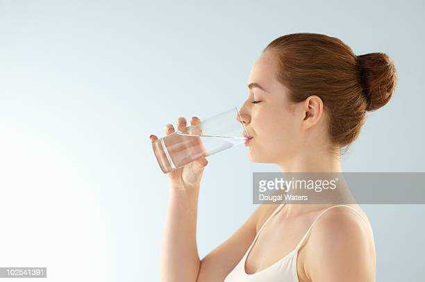 young woman drinking glass of water. - trinkwasser stock-fotos und bilder