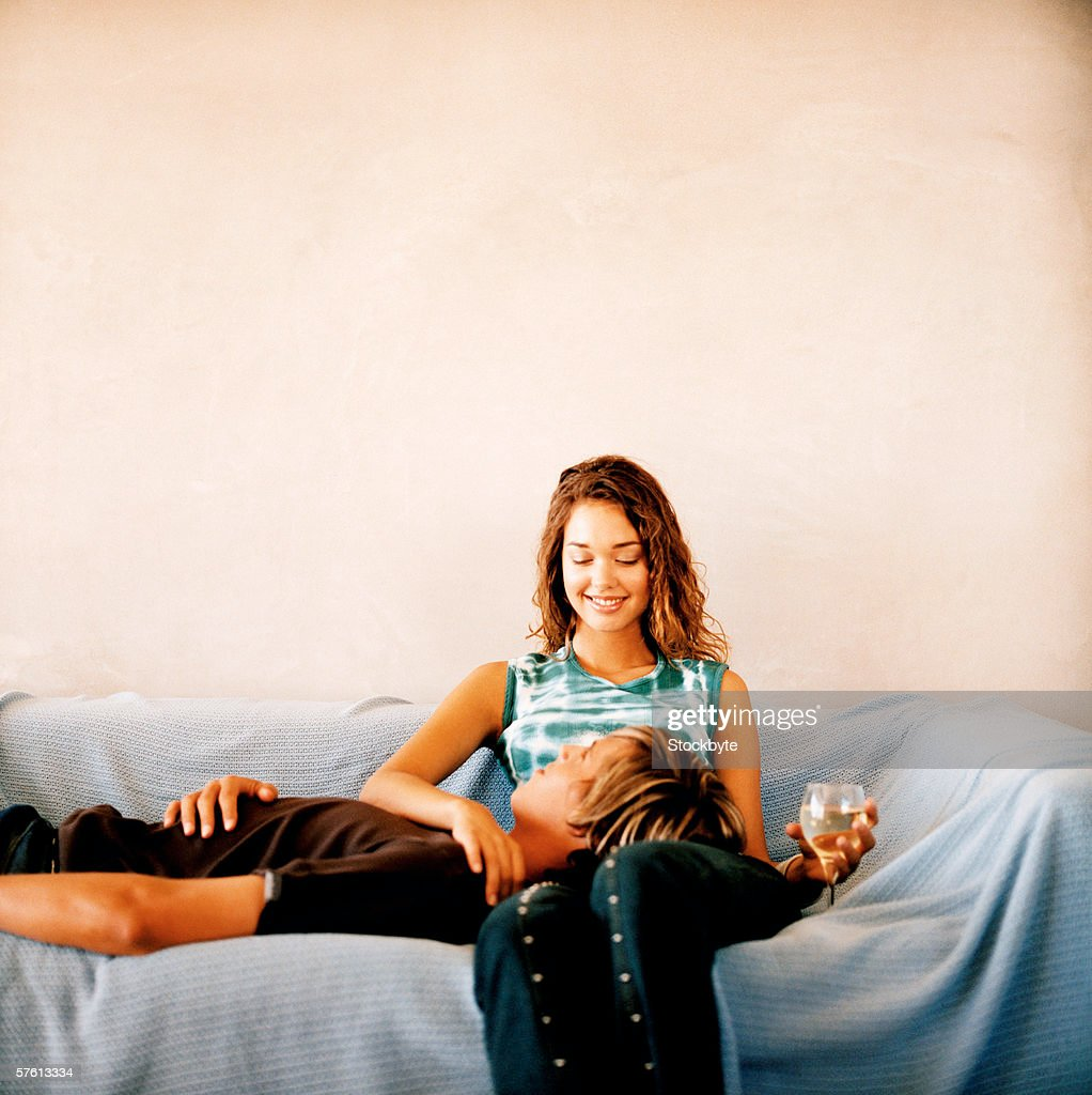 Young woman drinking glass of wine with young man lying on couch with his head on woman's lap : Stock Photo