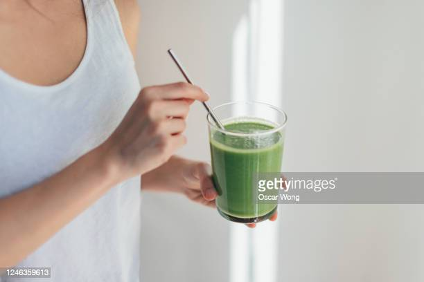 young woman drinking green juice for cleanse diet - refreshment stock pictures, royalty-free photos & images