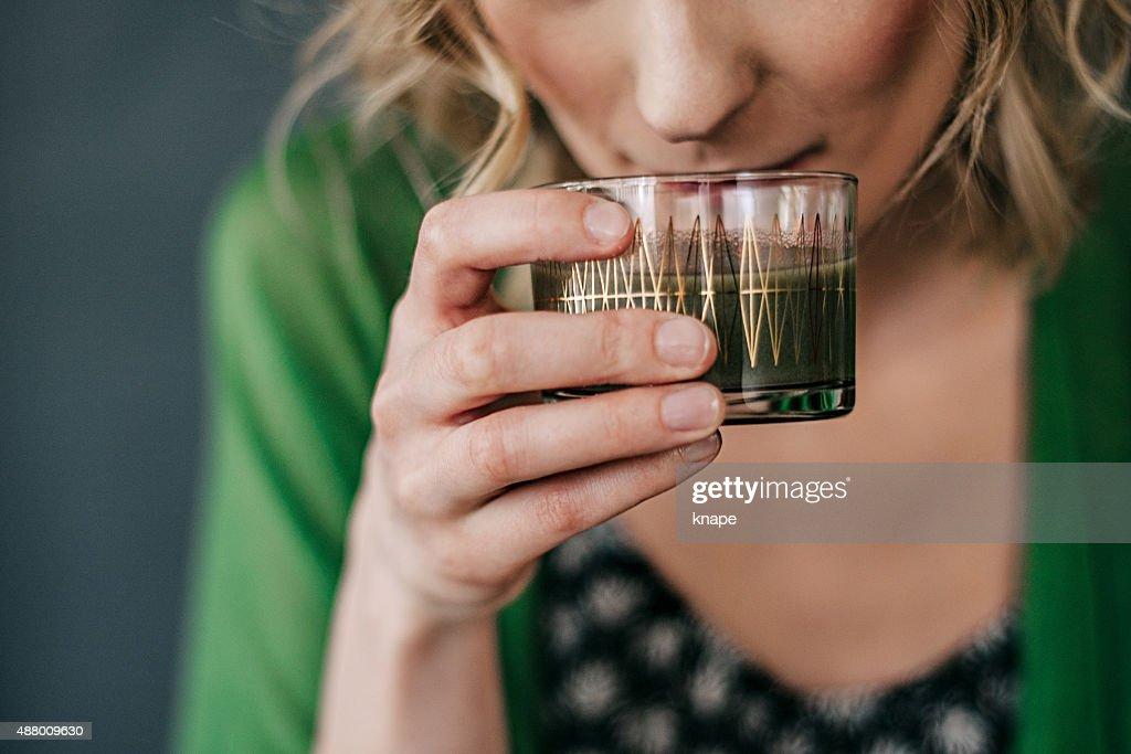 Junge Frau trinken grünen Saft : Stock-Foto