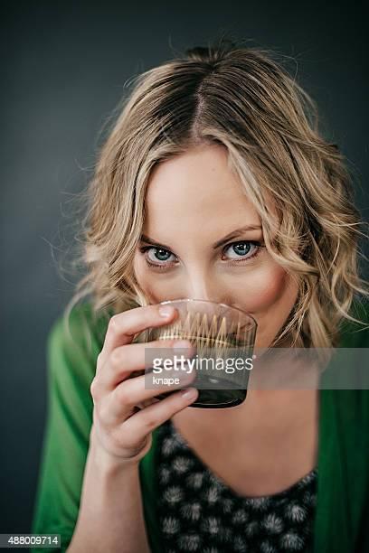 Junge Frau trinken grünen Saft