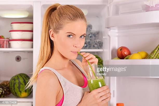 Junge Frau trinken grünen smoothie