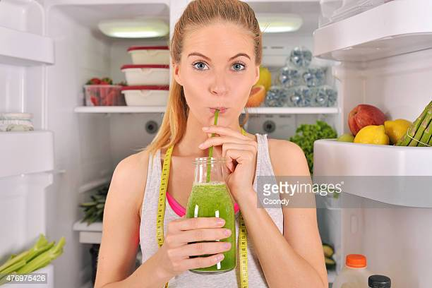 Young woman drinking green smoothie