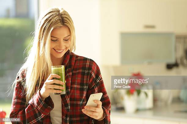 Young woman drinking health drink with mobile
