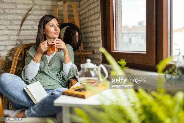 young woman drinking her winter tea and welcoming new day - ceremony stock pictures, royalty-free photos & images