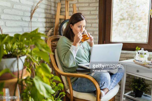 young woman drinking her winter tea while working at home - ceremony stock pictures, royalty-free photos & images