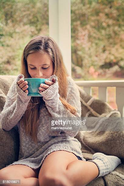 Young woman drinking hot beverage outdoors in autumn.