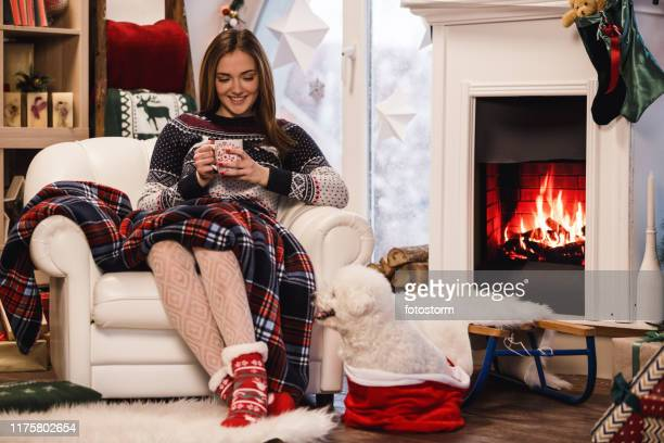 young woman drinking hot chocolate by the fireplace - hairy girl stock pictures, royalty-free photos & images
