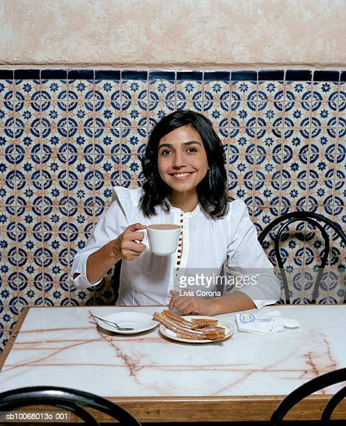 young woman drinking hot chocolate with mexican churro, portrait - churro stock photos and pictures