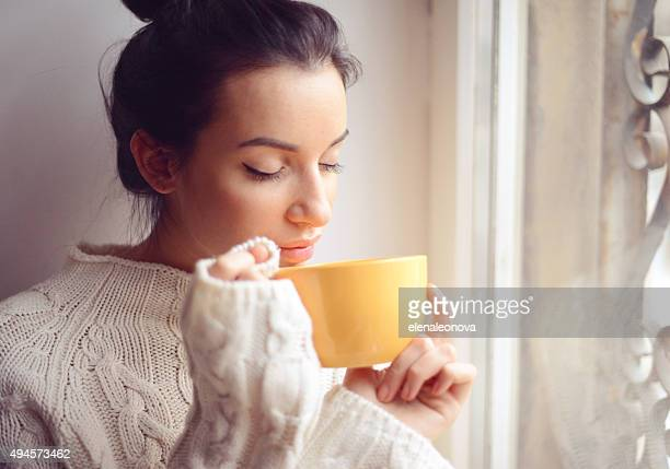 Young woman drinking hot coffee near the window