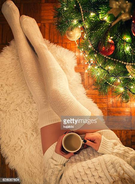 young woman drinking hot coffee on christmas night - nylon feet stock photos and pictures