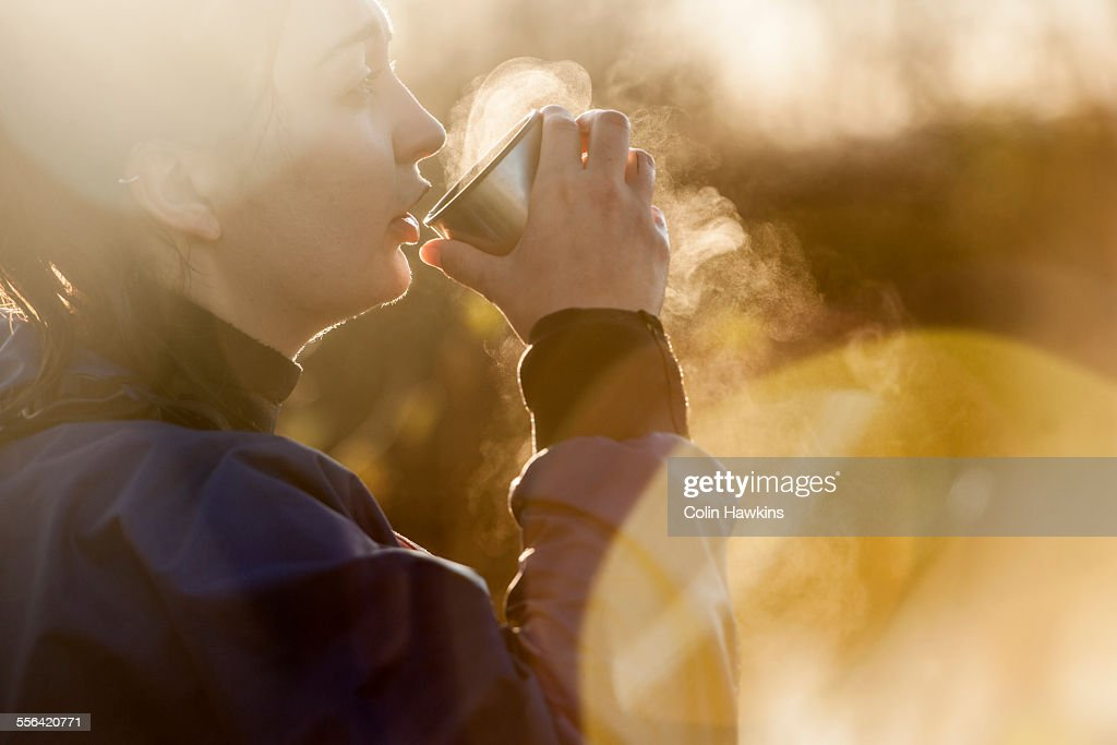 Young woman drinking hot drink in sunlight : Stock Photo