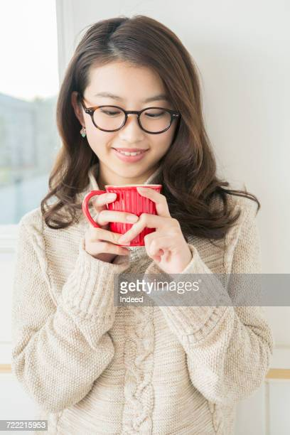 young woman drinking hot drink - 下を向く ストックフォトと画像