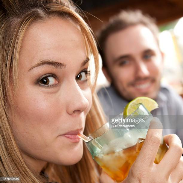 Young Woman Drinking Iced Drink With Her Husband at Restaurant