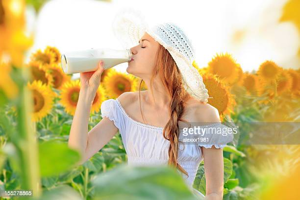 Young woman drinking milk in sunflower field