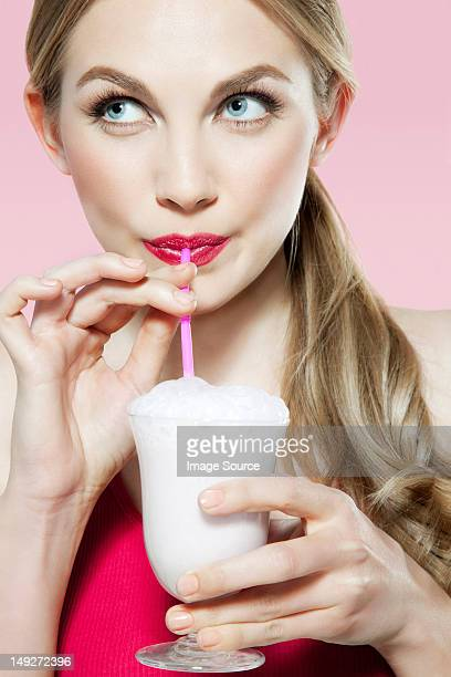 Young woman drinking milk shake