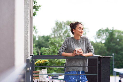 Young woman drinking morning coffee on the balcony - gettyimageskorea