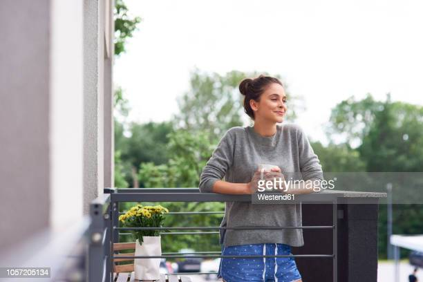 young woman drinking morning coffee on the balcony - ochtend stockfoto's en -beelden