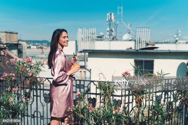 young woman drinking orange juice at the terrace - women in slips stock photos and pictures