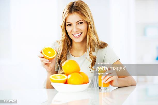 Young woman drinking orange juice.