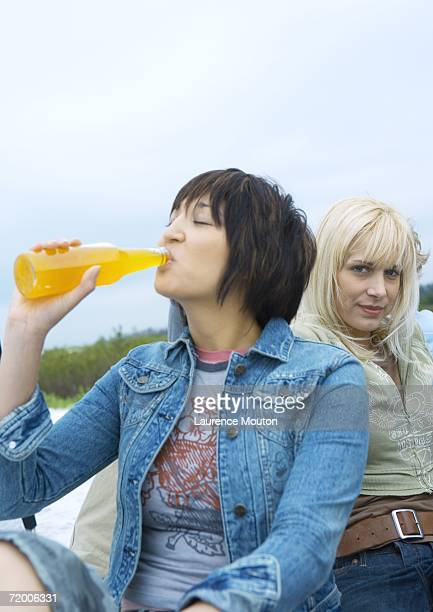 Young woman drinking orange soda