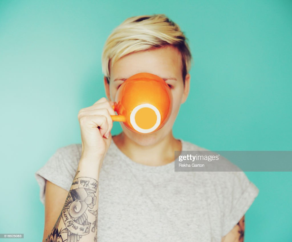 Young woman drinking out of an orange cup : Stock Photo