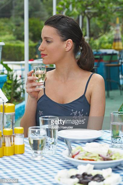 Young woman drinking outside at restaurant table.