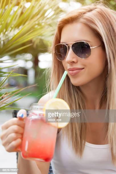 Jeune femme de boire du jus de framboise à l'extérieur