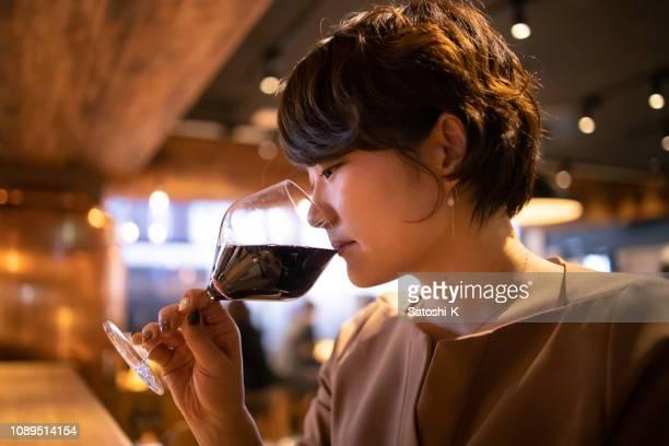 若い女性飲む赤ワイン ・ バーで - ショートヘア ストックフォトと画像